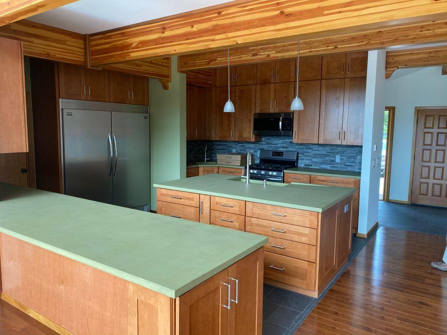 Finished kitchen area with green countertops and wooden beams